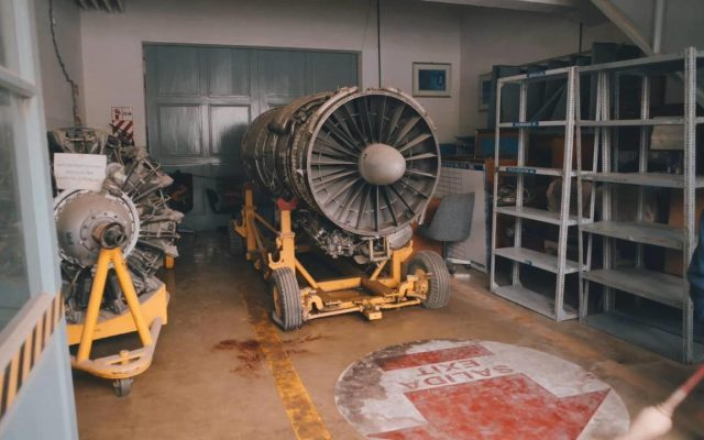 A dusty, stripped down airplane engine sits atop a wheeled yellow metal frame in a storage room. Empty metal shelves line the wall to the right, and another airplane component sits on another yellow frame to the left. On the floor in front of the engine, a large peeling red and white sticker reads 'SALIDA EXIT' with an arrow pointing forwards. Half out of frame, a man in blue overalls and a red cap sweeps the floor.