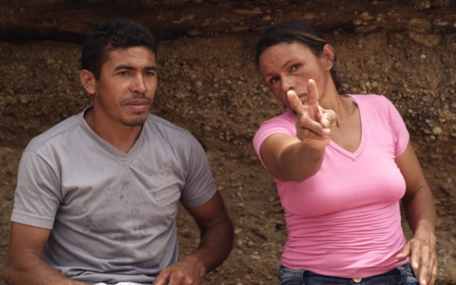 A man and woman sit side by side outdoors, facing towards us. They are visible from the waists up and fill most of the frame. The woman sits to the right of the image and wears a pink t-shirt. Her right arm is outstretched in front of her and she is making a 'V' sign with her fingers. She tilts her head towards the man and looks towards her fingers, as if she is demonstrating something to him. The man sits to the left of the image and wears a grey t-shirt. He is attentively looking at the woman's outstretched hand.
