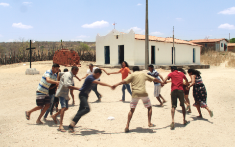 On a bright sunny day, a group of men and women hold hands and run in a circle anti-clockwise. They wear shorts and t-shirts in various colours. The ground beneath their bare feet is bare and sandy. In the background there is a long, single storey white brick building with a beige coloured roof. The sky is blue with some tiny, wispy white clouds.
